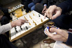 Tea and Games. Close-up of hands holding and stirring a glass of tea with people playing board games in the background. Taken in a male dominated cafe in Stock Image