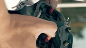 Hands holding a transmitter controlling FPV drone. Close up of hands holding a transmitter and controlling FPV drone. Drone control training process in sunny day stock footage