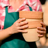 Close-up hands holding two clay pots Royalty Free Stock Photo