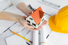 Close up of hands with house model above blueprint Stock Images