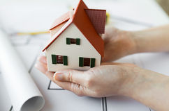 Close up of hands with house model above blueprint Royalty Free Stock Photography