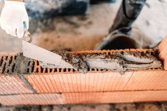 hands of industrial bricklayer installing bricks on construction site stock photo