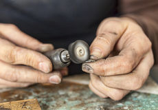 Hands of a Jeweller. Close-up of the hands of a jeweller polishing a piece of silver Stock Photo