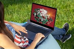Woman playing poker on laptop pc computer, sitting in park on green grass sunshine lawn outdoors. Close up hands on keyboard. Woman playing poker on laptop pc stock image