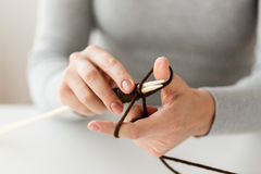 Close up of hands knitting with needles and yarn. People and needlework concept - close up of woman hands knitting with needles and brown yarn Royalty Free Stock Photos
