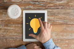 Close up of hands with ligting bulb on tablet pc Stock Image