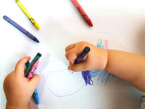 Close up of the hands of a little child drawing a flower with color pencils Royalty Free Stock Image