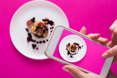 Close-up of hands making food photo. Top view close-up of female hands making flat lay food photo with phone for restaurant menu or social network. Oatmeal royalty free stock photos