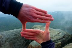 Close up of hands making frame gesture. Blue misty valley bellow rocky peak. Rainy spring day. Stock Photography