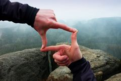 Close up of hands making frame gesture. Blue misty valley bellow rocky peak. Rainy spring day. Royalty Free Stock Photos