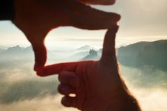 Close up of hands making frame gesture. Blue misty valley bellow rocky peak. Sunny spring daybreak in misty rocky mountains. Royalty Free Stock Image