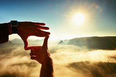 Close up of hands making frame gesture. Blue misty valley bellow rocky peak. Sunny spring daybreak in misty rocky mountains. Royalty Free Stock Images