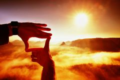 Close up of hands making frame gesture. Blue misty valley bellow rocky peak. Sunny spring daybreak in misty rocky mountains. Royalty Free Stock Photography