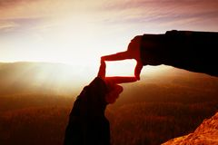 Close up hands making frame gesture. Orange misty valley bellow. Sunny spring daybreak in mountains. Royalty Free Stock Images