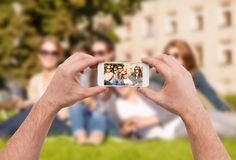 Close up of hands making picture of group of teens Stock Images