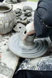 Close-up of hands making pottery from clay on a wheel. Stock Photos