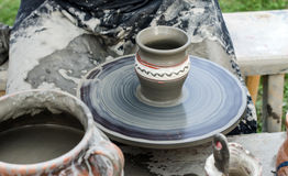 Close-up of hands making pottery from clay on a wheel. Royalty Free Stock Photography