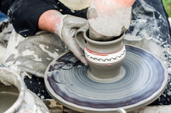 Close-up of hands making pottery from clay on a wheel. Royalty Free Stock Images