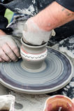 Close-up of hands making pottery from clay on a wheel. Royalty Free Stock Photo