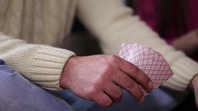 Close-up hands of male player who playing cards with the company. stock video footage