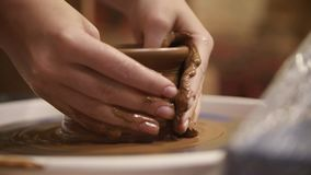 Hands of a Potter. Close-up hands of a male potter in apron molds bowl from clay. Hobby,lifestyle concept stock video footage