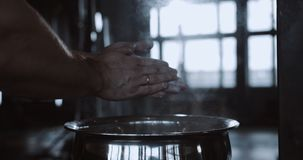 Close-up hands of male weight lifter clapping with talc powder before exercising in large hardcore gym hall slow motion. Fitness and heavy weight sports stock video