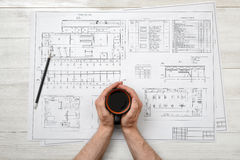 Close-up hands of man holding cup coffee over drawing layout in top view. Close-up hands of man holding a cup of coffee over drawing layout in top view Stock Images