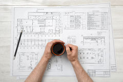 Close-up hands of man holding cup coffee over drawing layout in top view Royalty Free Stock Images