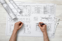 Close-up hands of man holding an engineering divider over drawing plan in top view. Engineering work. Measurement Royalty Free Stock Images