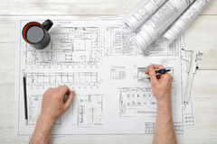 Close-up hands of man holding an engineering divider over drawing plan in top view. Workplace of architect or constructor. Engineering work. Construction and Stock Photo