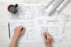 Close-up hands of man holding an engineering divider over drawing plan in top view. Workplace. Engineering work. Construction and architecture. Architect Stock Photos