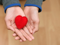 Close up hands a man holding and person red heart on wood table. Royalty Free Stock Images