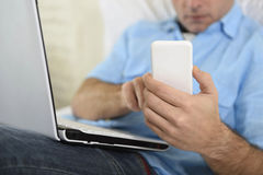 Close up hands of man lying on bed couch using mobile phone and computer working from home Stock Image