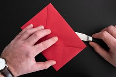 Hands of man opening red envelope with paper knife royalty free stock photo