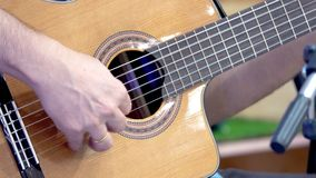 Close up of hands of a man playing a classic guitar on stage.