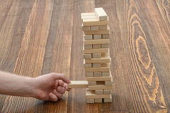 Close-up hands of man pulls out wooden bricks. Royalty Free Stock Photography