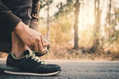 Close-up hands of man tying shoelace during running on the road for health. Color of vintage tone selective and soft focus royalty free stock images