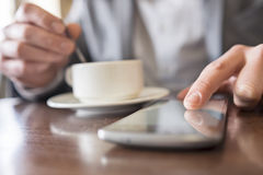 Close-up hands man using cell phone in coffee bar Royalty Free Stock Photography