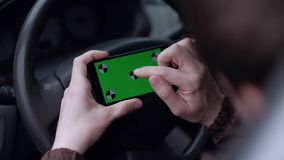 Male driver using smartphone  with green screen in the car. Close up - hands of man using smartphone  with green screen  in the car stock video footage