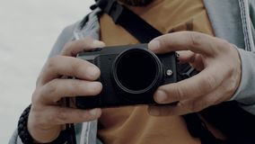 Close-up of the hands of a man who holds the camera and takes a photo by pressing a button. photographer takes a photo. 4k. 4k. Video. 60 fps stock video footage