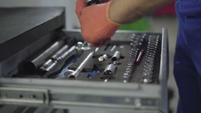 Close up hands of mechanic in gloves take the tool out of the box and collects parts together. Worker fixing automobile