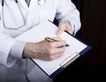 Close-up hands of a medical doctor, the doctor signs a handle documents. Doctor writes medical history. write a Royalty Free Stock Photo