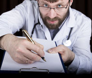 Close-up hands of a medical doctor, the doctor signs a handle documents. Doctor writes medical history. write a Stock Photography
