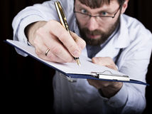 Close-up hands of a medical doctor, the doctor signs a handle documents. Doctor writes medical history. write a Royalty Free Stock Images