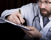Close-up hands of a medical doctor, the doctor signs a handle documents. Doctor writes medical history. write a Stock Images
