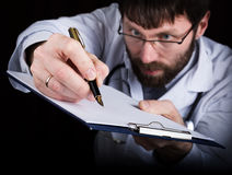 Close-up hands of a medical doctor, the doctor signs a handle documents. Doctor writes medical history. write a Stock Photo