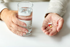 Close up of hands with medicine pills and water Stock Images