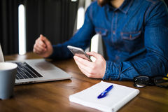 Close up hands multitasking man using laptop and cellphone connecting wifi, notebook and coffee cup Royalty Free Stock Images