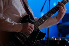 Close-up of the hands of a musician who holds a guitar. The guitarist plays the electric guitar. Rock musician. Jazz music concert stock photos