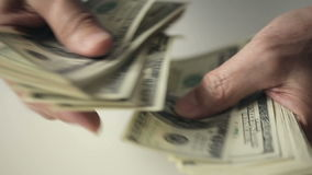Close up of hands of an old man counting hundred dollar bills at a table